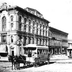 Mule-drawn streetcars carry passengers past clock on Main and 100 South in 1873. The clock still graces that corner.