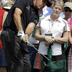 Phil Mickelson chips out of the gallery on the second hole during the first round the Masters golf tournament Thursday, April 5, 2012, in Augusta, Ga.