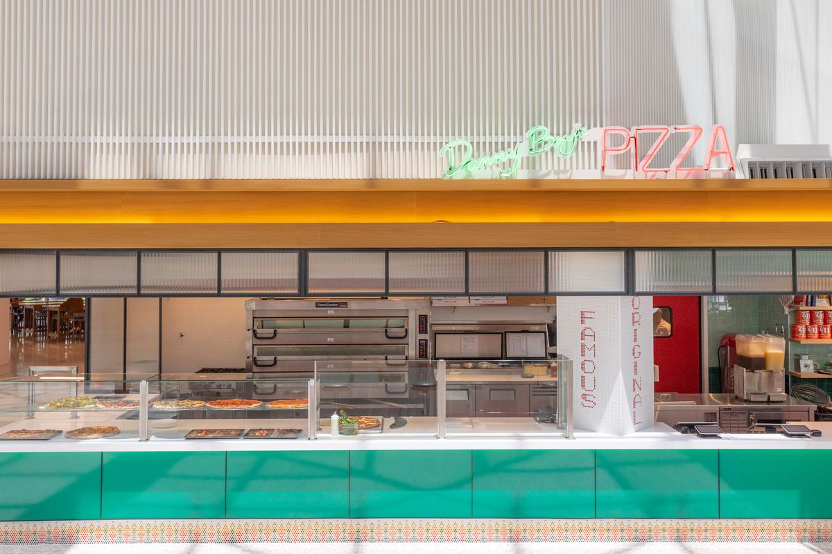 A straight-on look at a food hall kiosk for selling pizzas, with neon lights.