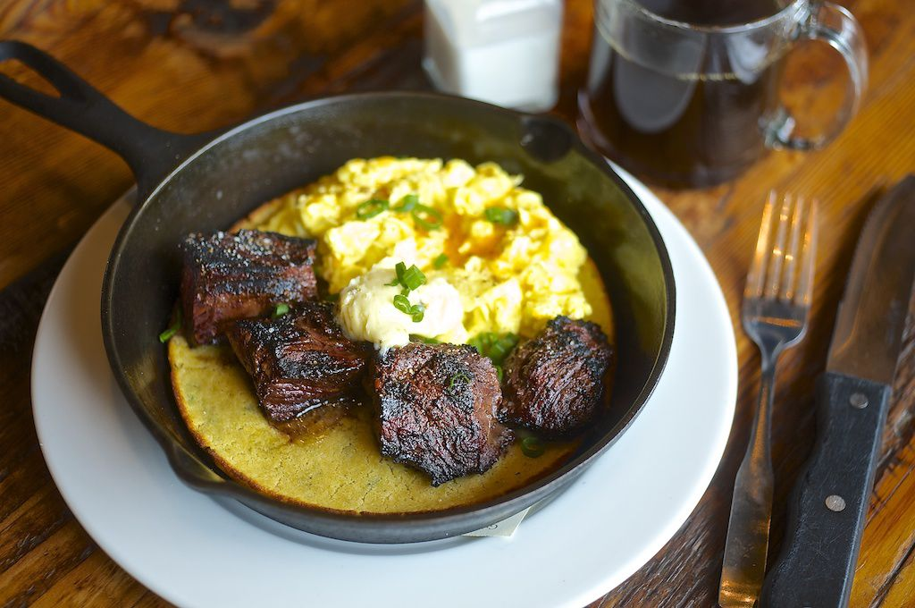 A cast iron comes with a yellow corn cake, topped with hunks of steak and a pile of soft scrambled eggs. It arrives on its own white plate, with a steak knife and fork next to it.