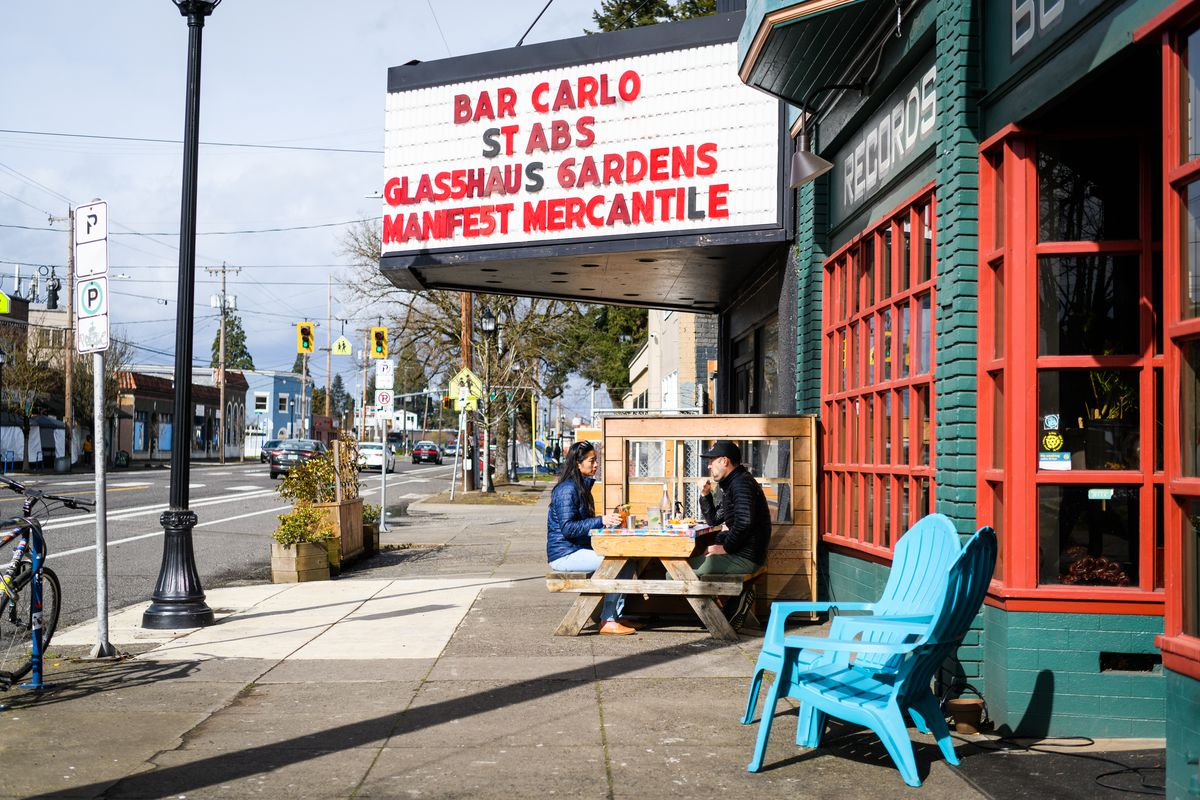 "A teal-and-red-painted bar displays a marquee that reads ""Bar Carlo Stabs Glasshaus Gardens Manifest Mercantile."" Customers sit under the marquee at a picnic table."