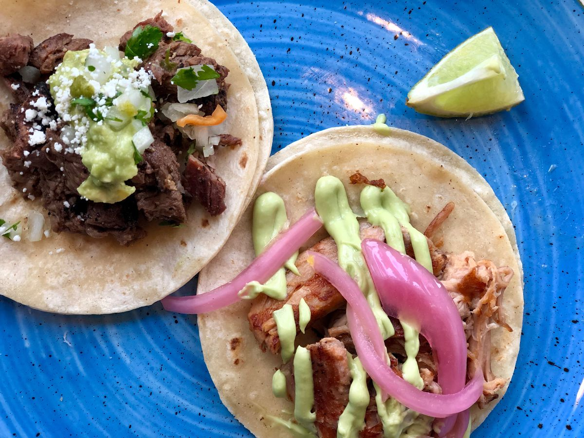 Tacos with salsa and lime at Que Bueno Serte in Denver.