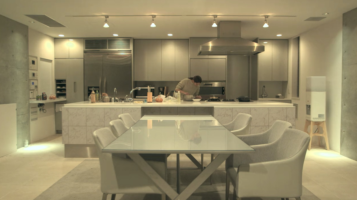 In the foreground is a table and chairs. There is a grey area rug under the table. In the background is a kitchen with a kitchen island. A person is preparing a meal on the kitchen island while looking at their phone.