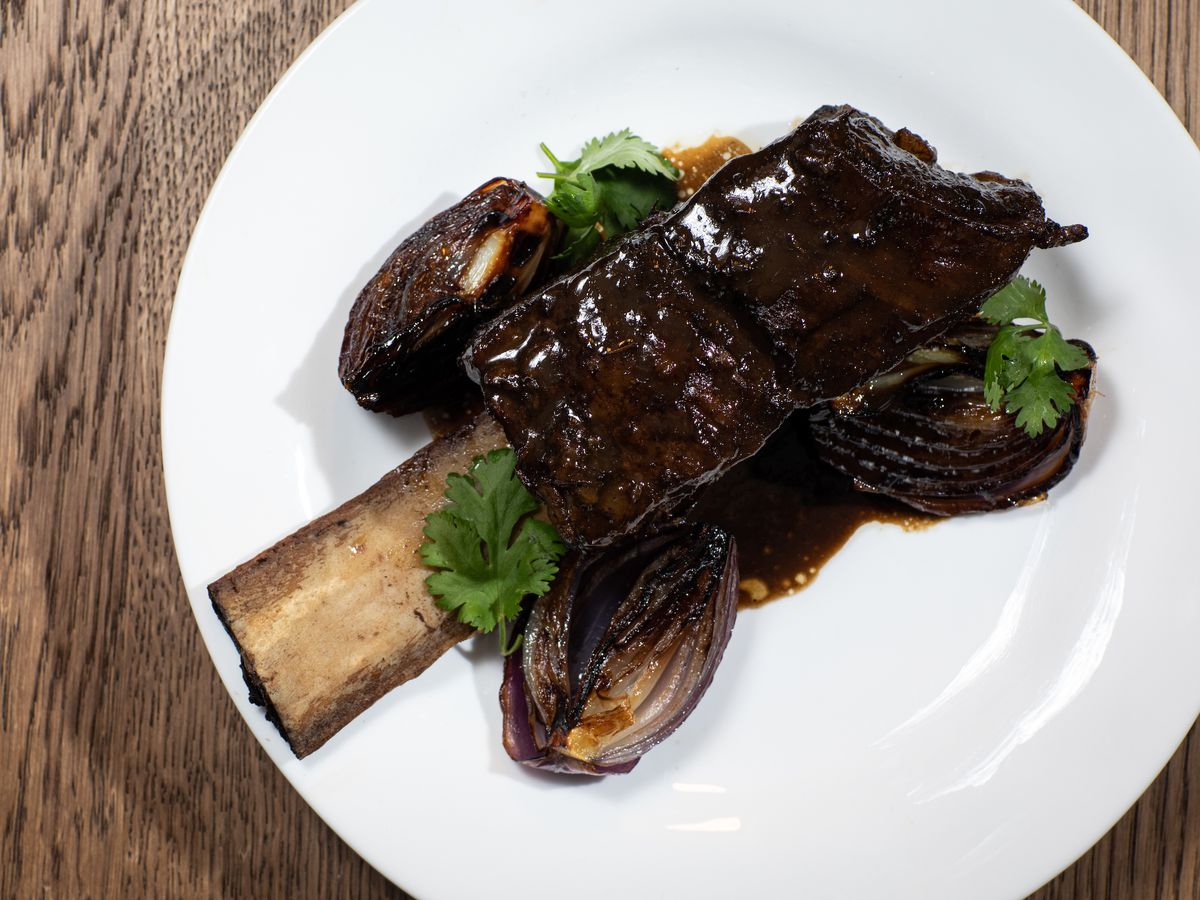 A short rib on the bone with grilled quarters of red onions and green parsley garnish on a white plate set on a wooden table