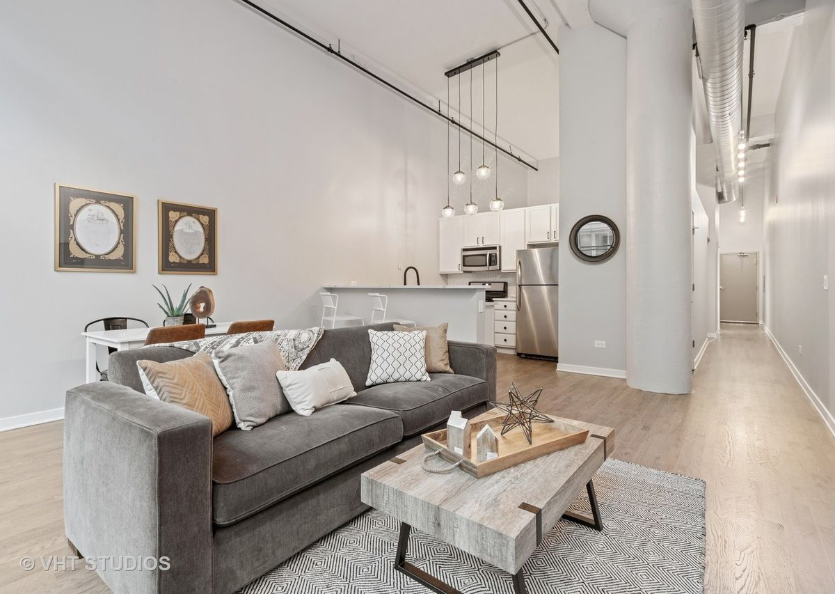 A high-ceiling loft unit with a gray couch and white kitchen with stainless steel appliances.
