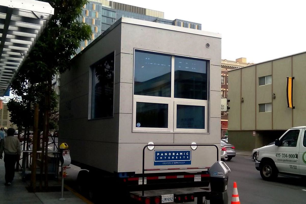 A tiny, prefab apartment sitting on the back of a truck parked in SoMa.