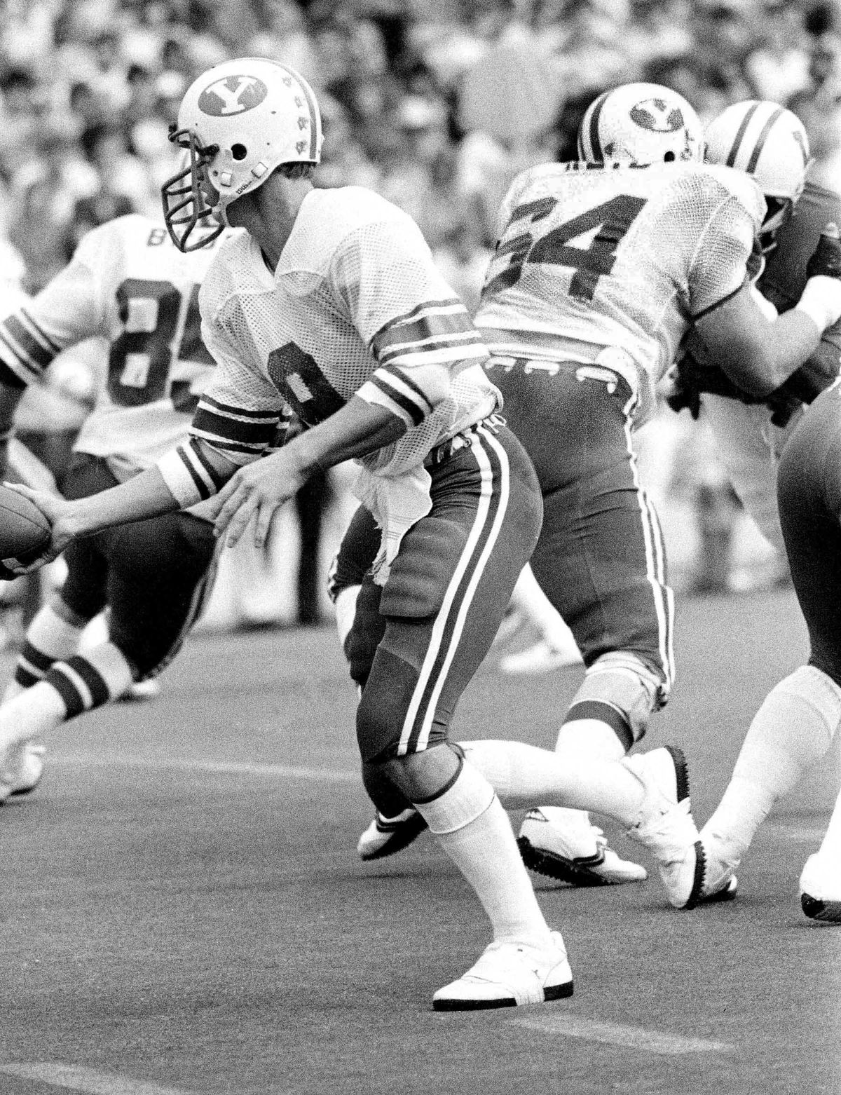 BYU offensive lineman Andy Reid, right, throws a block as quarterback Jim McMahon looks to hand off.