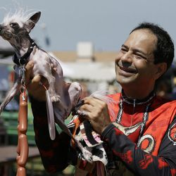 Dane Andrew of Sunnyvale, Calif., holds up his dog, Rascal, a Chinese crested, before the start of the World's Ugliest Dog Contest at the Sonoma-Marin Fair Friday, June 23, 2017, in Petaluma, Calif.