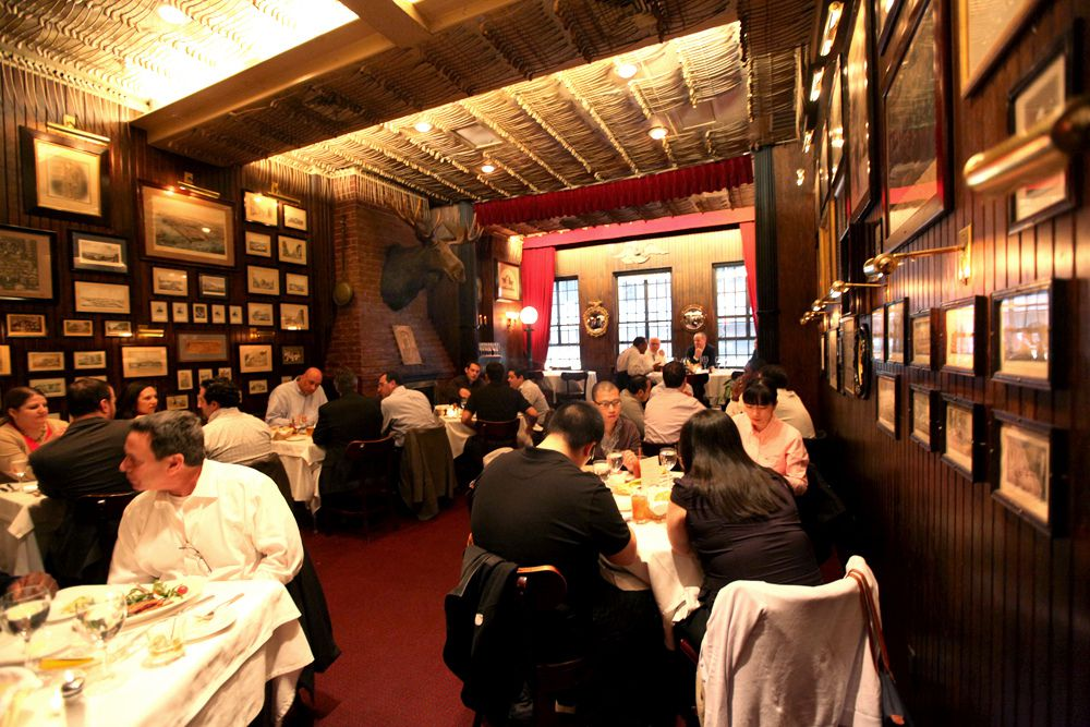 Keens dark dining room has framed memorabilia and photos on all the walls