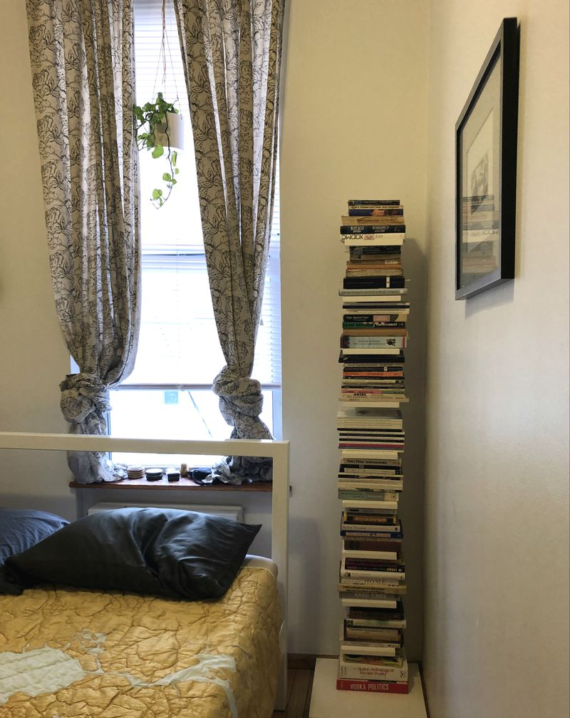 A room has a tall bookshelf in one corner, next to a bed with yellow bedding in front of a window.