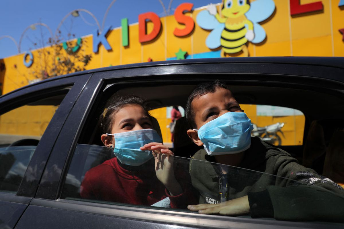 Palestinian children wearing masks look out of a car window in Gaza City on March 7, 2020, following a government decision to suspend schools due to fears of the spread of COVID-19.