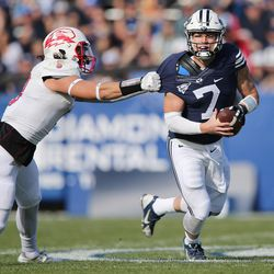 Brigham Young Cougars quarterback Taysom Hill (7) gets aways from Southern Utah Thunderbirds running back Pete Williams (6)  in Provo on Saturday, Nov. 12, 2016.