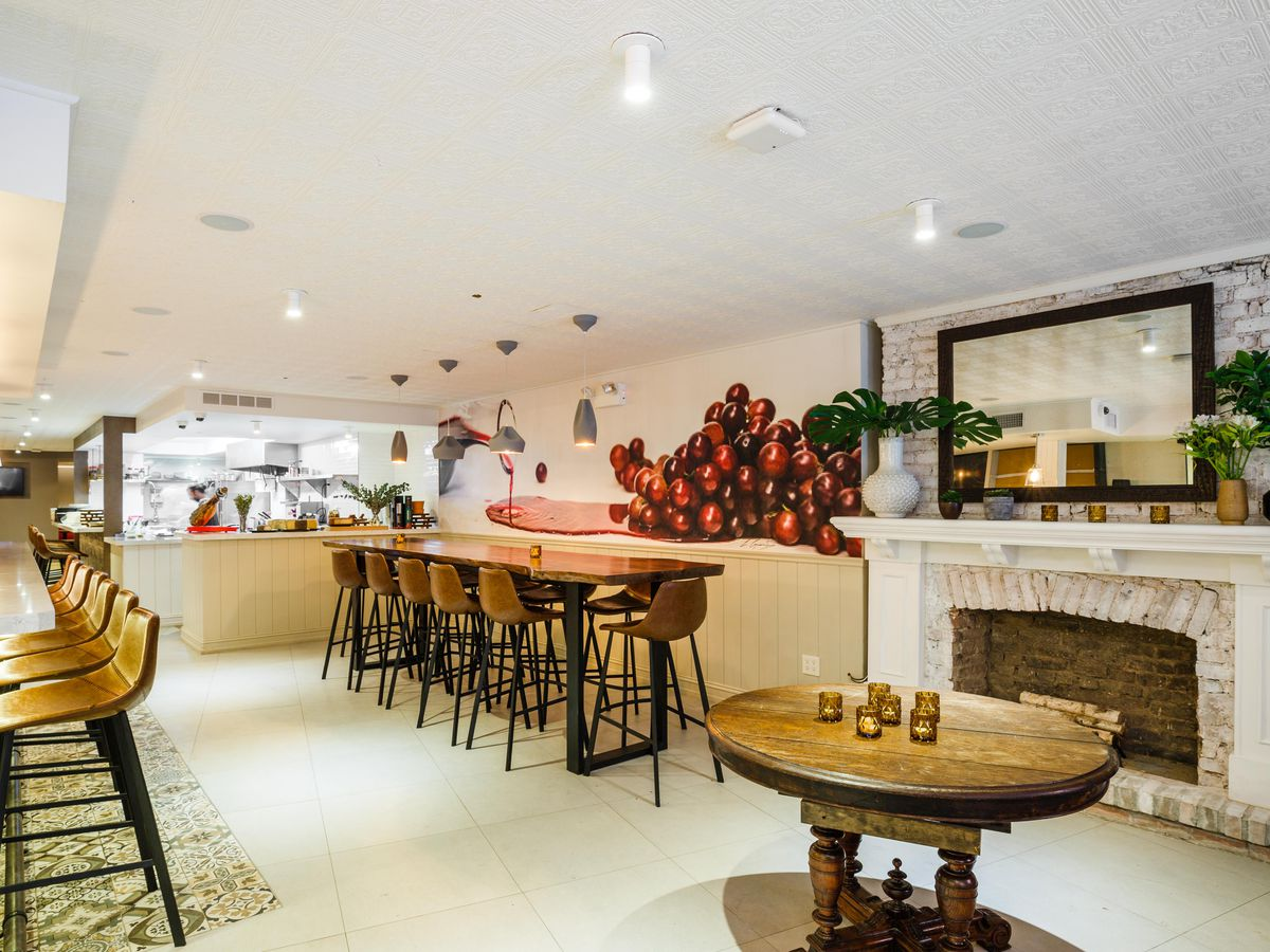A clean, white restaurant interior with light wooden tables
