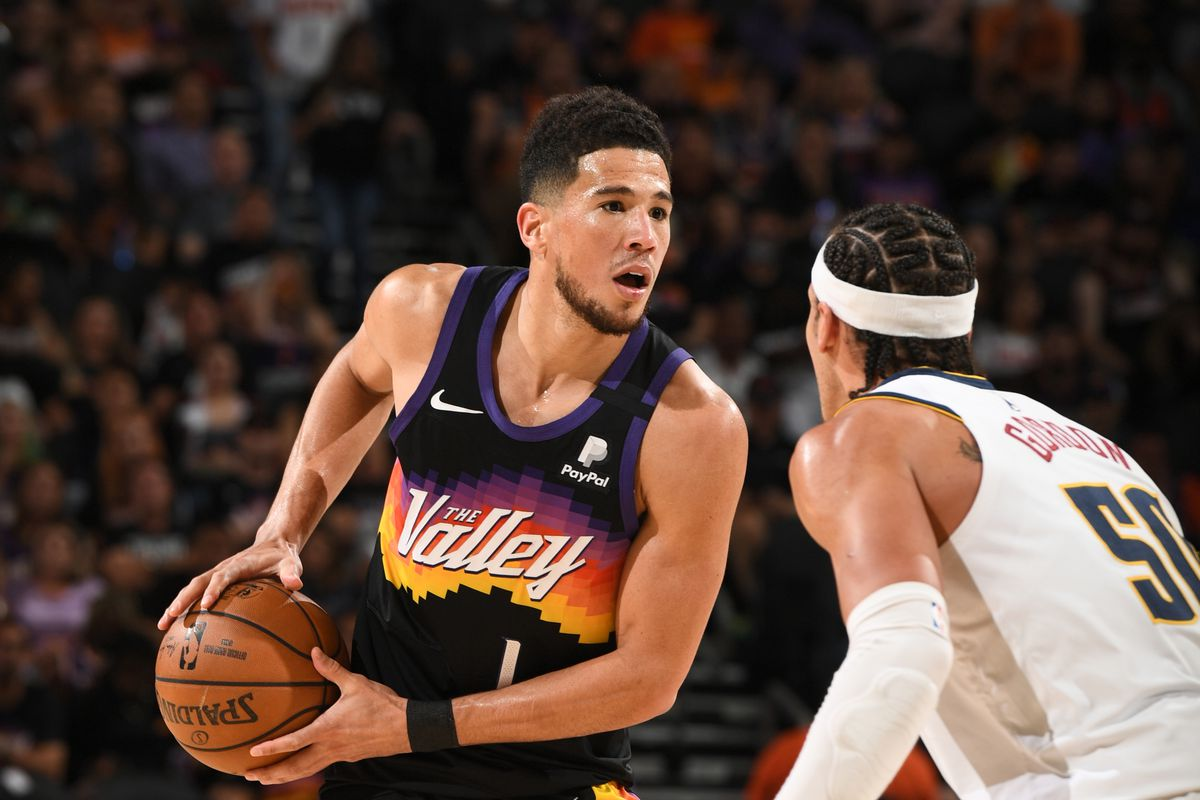 Aaron Gordon #50 of the Denver Nuggets plays defense on Devin Booker #1 of the Phoenix Suns during Round 2, Game 1 of the 2021 NBA Playoffs on June 7, 2021 at Phoenix Suns Arena in Phoenix, Arizona.