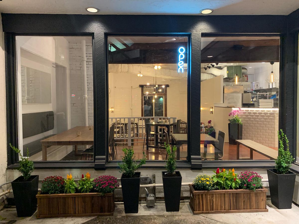 """The exterior of Secret Savory in Ballard shows a neon """"open"""" sign and flowers lining the windows."""