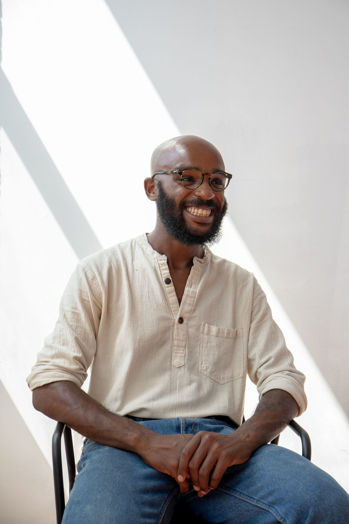 A man in a white shirt and light blue jeans with a bald head and wire-framed glasses