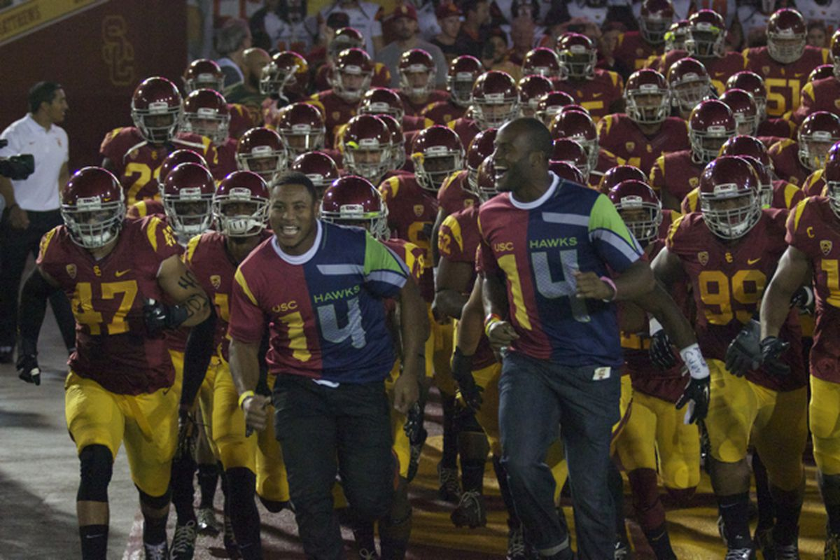 Malcolm Smith and Mike Morgan lead the Trojans out of the tunnel.