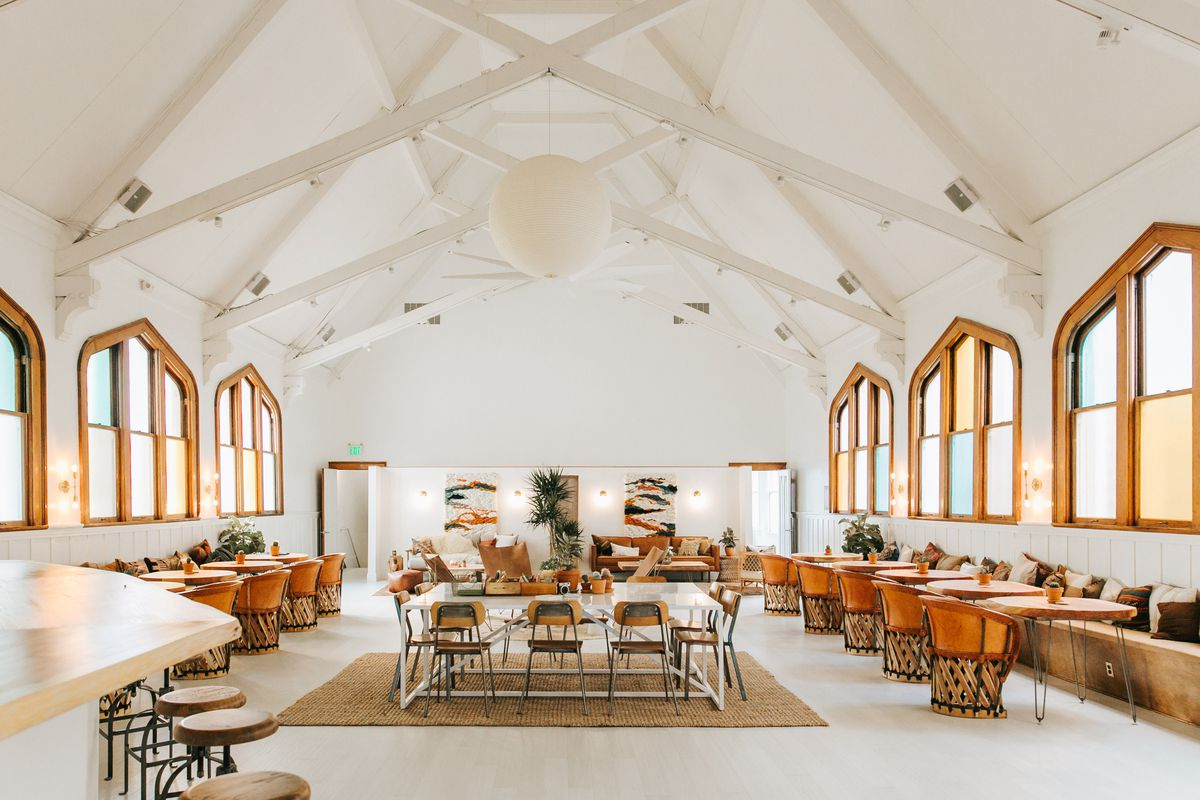 The interior of the co-working space The Assembly in San Francisco's Mission District. There are multiple chairs and tables. The ceilings are high with white structural beams. There are multiple windows.