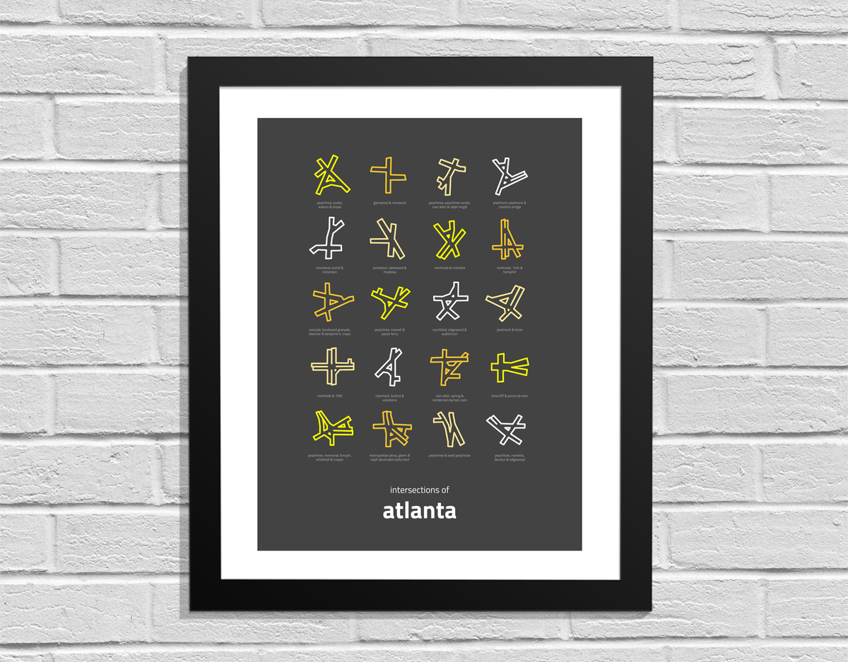 A framed work of art hangs on a white brick wall. The art has words on it which read: Intersections of Atlanta. There are various assorted patterns above the words.