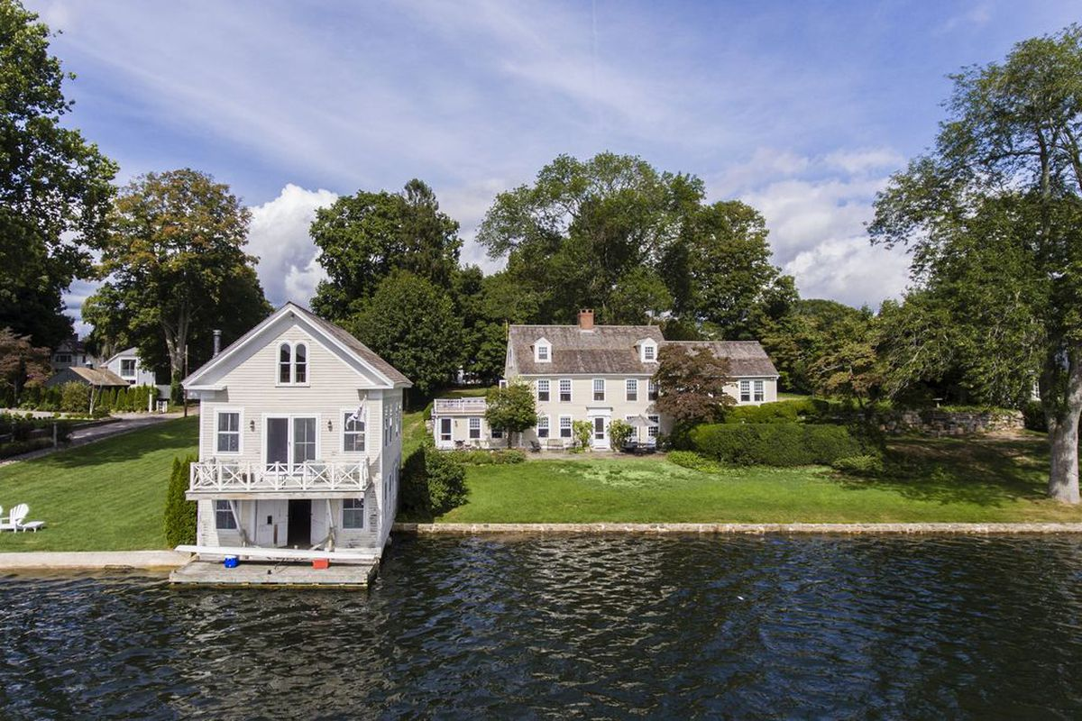 Shot of a two-story boathouse and a large house in the background set right on the water.
