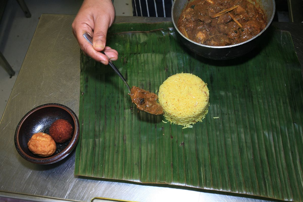 Black pork curry is spooned on to a charred banana leaf, next to yellow steamed rice