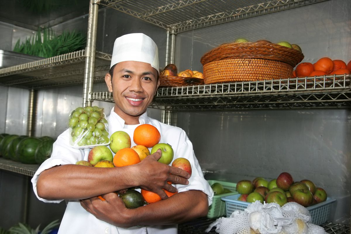 A cook holding produce in a walk-in refrigerator.
