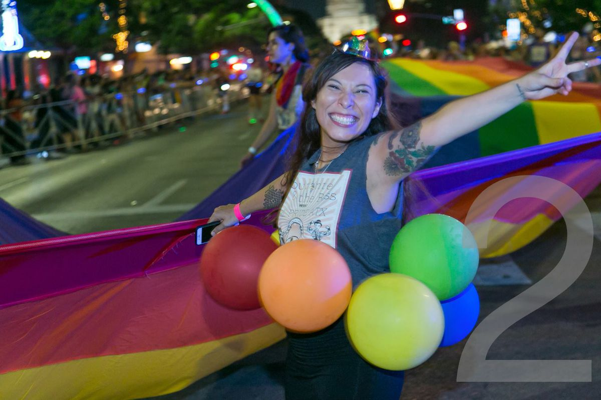 A smiling woman with light brown skin and straight dark hair wearing rainbow balloons,  holding a banner, and throwing a peace sign.