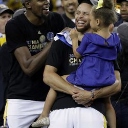 Golden State Warriors guard Stephen Curry, center, holds his daughter Riley as they celebrate with forward Kevin Durant, left, after Game 5 of basketball's NBA Finals against the Cleveland Cavaliers in Oakland, Calif., Monday, June 12, 2017. The Warriors won 129-120 to win the NBA championship.