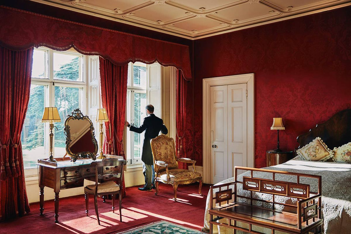 A butler stands near a window in a room with red walls and period furniture.