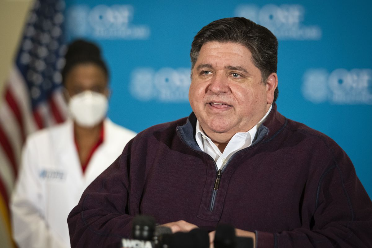 Gov. J.B. Pritzker speaks to reporters after a nurse administered Illinois' first five Pfizer-BioNTech COVID-19 vaccinations outside of Chicago to at OSF Saint Francis Medical Center in downstate Peoria last month. Pritzker called on the federal government to send reserve doses of the vaccine to states immediately.
