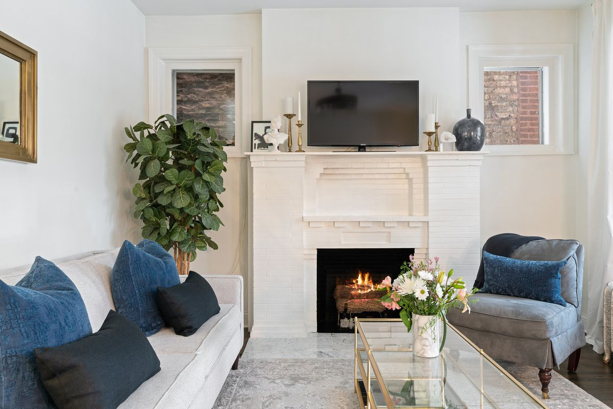 A living room with a white brick fireplace topped b a tv. The room has a sofa, fig tree, glass coffee table, and a gray chair.