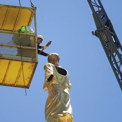 Workers from Mountain National Heavy Haul remove the lighting rod and attach a hook to the lightning-damaged Angel Moroni statue atop the Bountiful Utah Temple on Wednesday, June 1, 2016, in Bountiful. Lightning struck the statue on May 22, 2016.