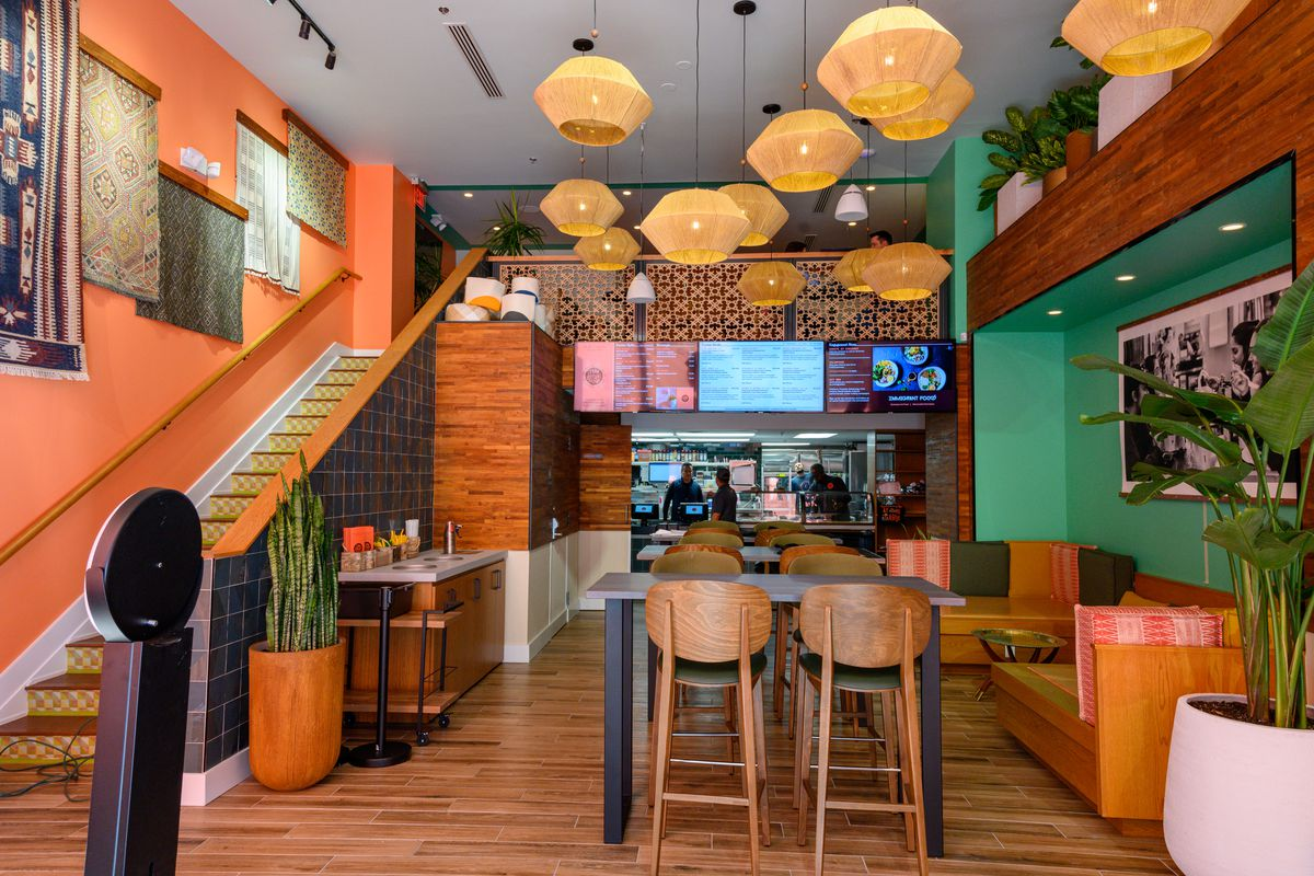 The interior of Immigrant Food includes a seating area in front of an ordering counter