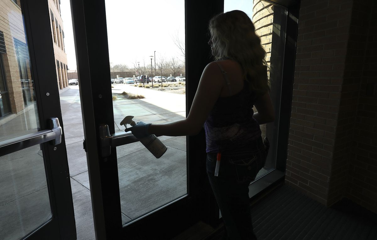 Salt Lake Community College custodian Shawna Grundtvig wipes down door handles on campus in Taylorsville on Tuesday, March 10, 2020. Utah colleges continue to make contingency plans in the wake of the spread of COVID-19. Some plans include moving exclusively to online classes.