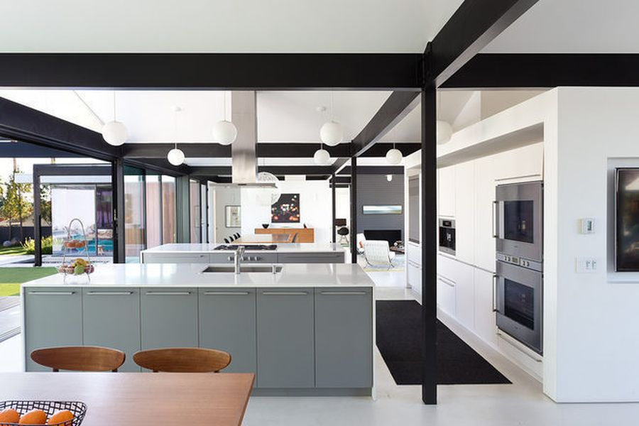 A midcentury modern kitchen with white walls and ceiling, grey cabinetry on the kitchen island, and a wooden table with chairs. There are black support beams.