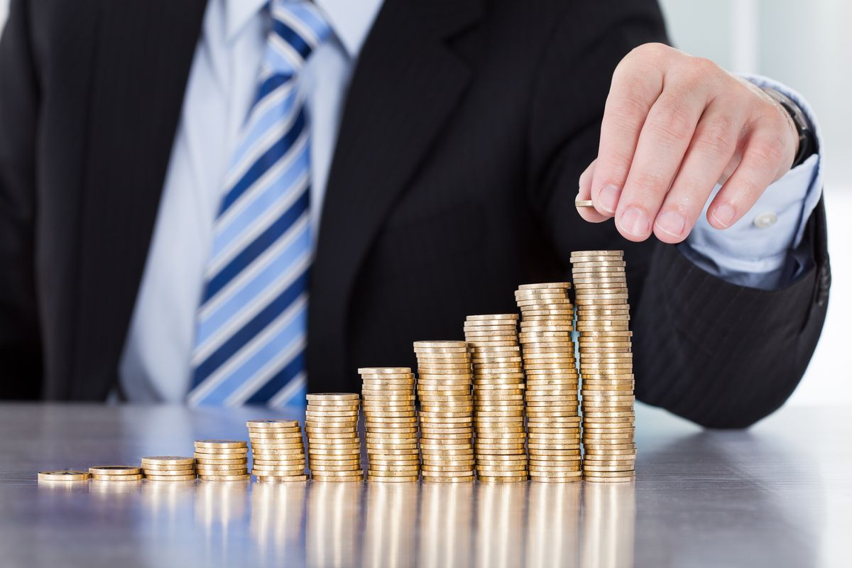 Man stacking coins up in growing piles