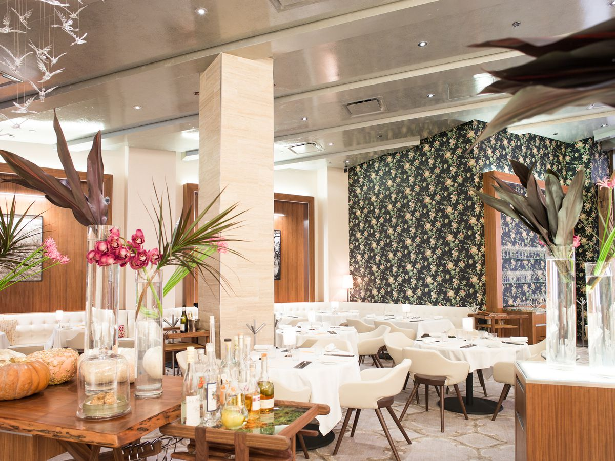 Gabriel Kreuther Restaurant's dining room with white chairs and a dark patterned wallpaper