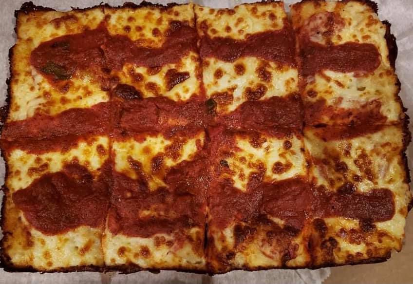 Overhead view of a cheese Detroit-style pizza on wax paper