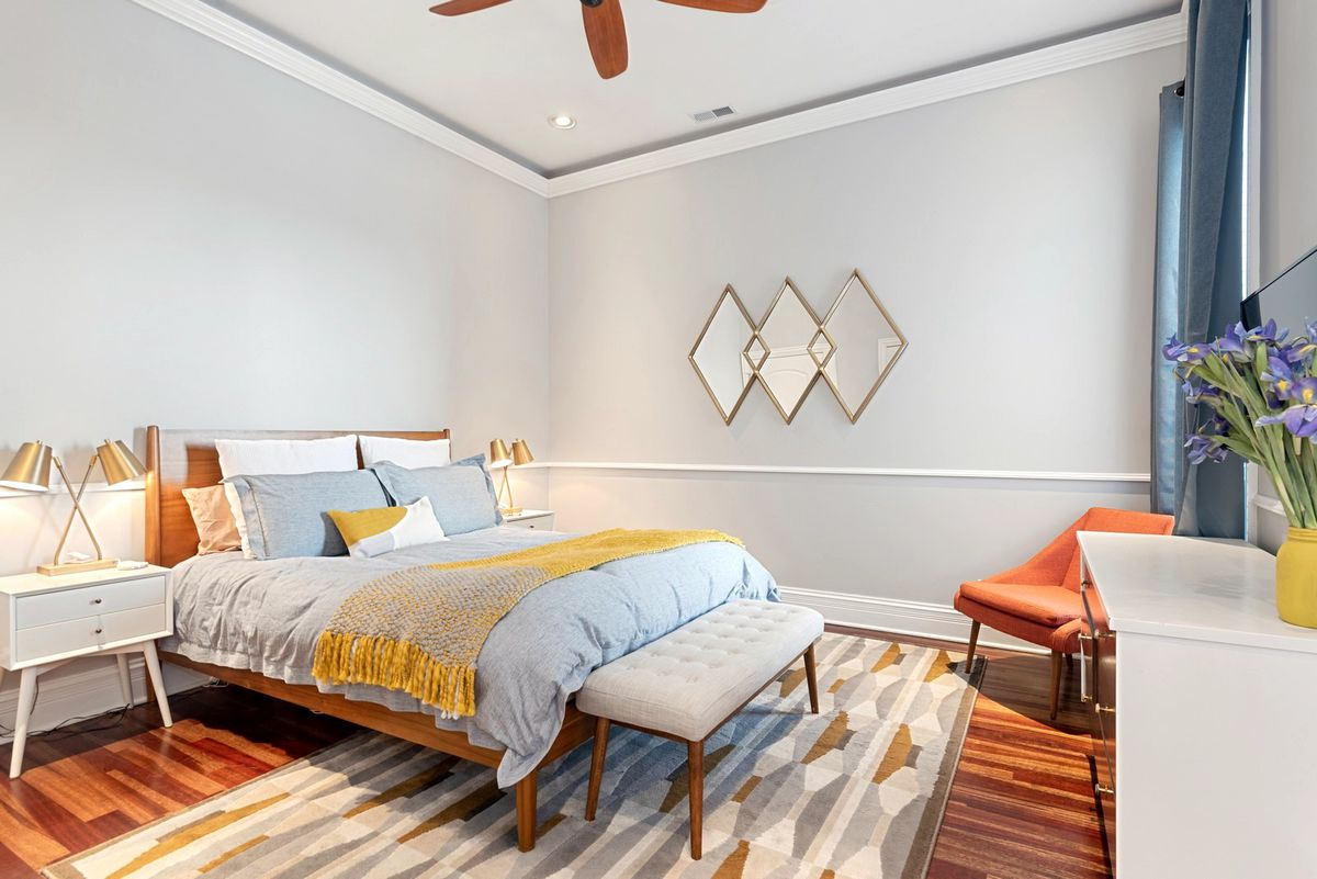 A wood framed bed with a light blue comforter centered on a wall next to white nightstands with brass lamps.