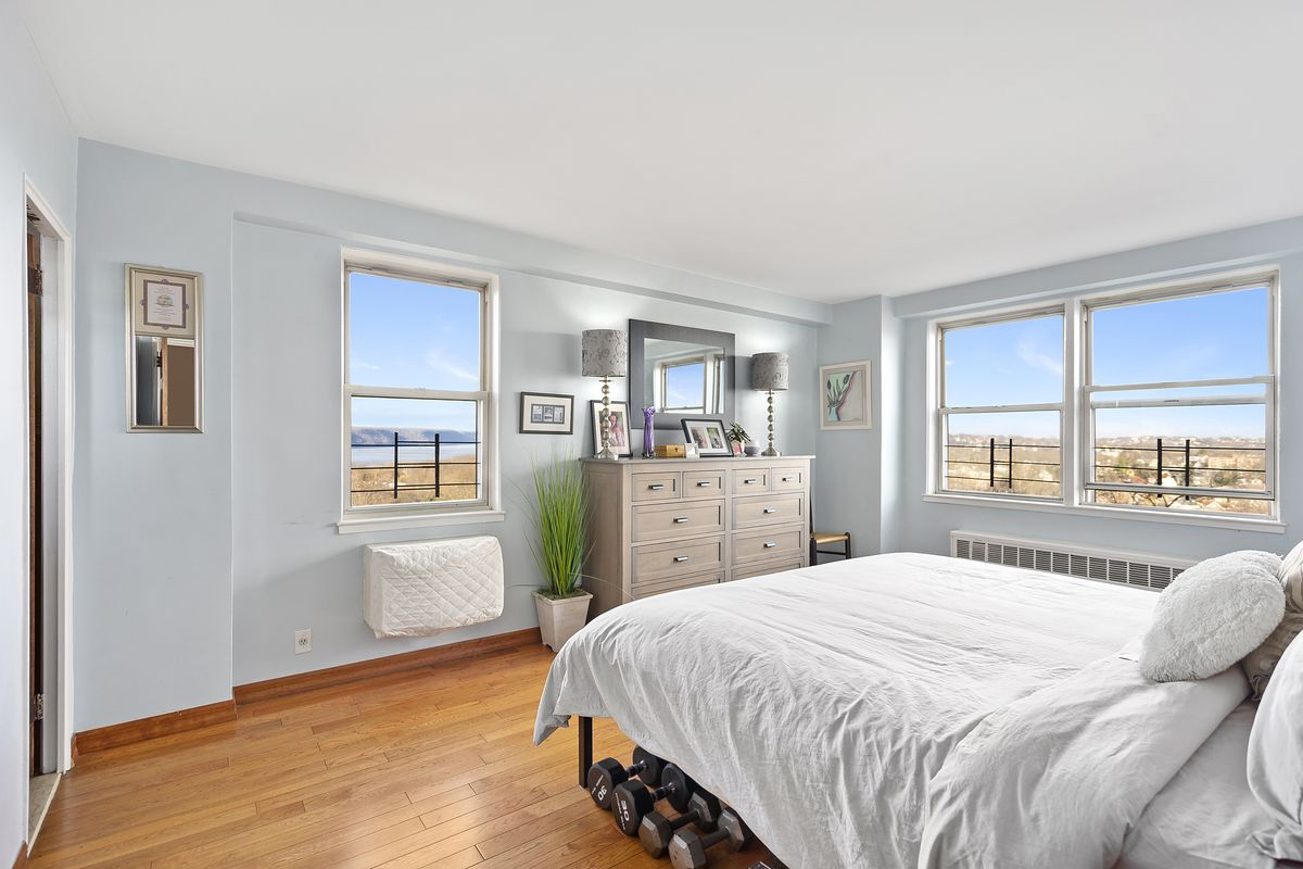 A bedroom with hardwood floors, a medium-sized bed, several windows, and light blue walls.