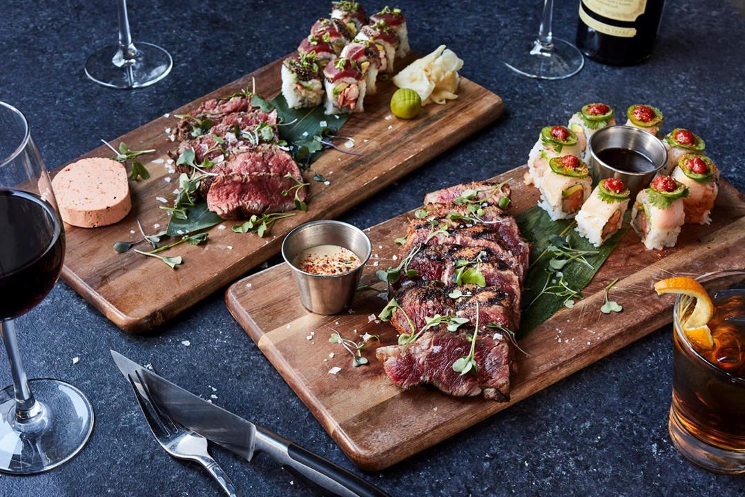Steak and sushi on a wooden cutting board