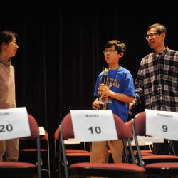 Seventh-grader Aaron Chang (center) from the Audubon Elementary School with his parents Susanna and Michael Chang after award ceremony where he received trophy for winning annual Citywide Spelling Bee Championship at the Lindblom Math and Science Academy on March 14, 2019. He will represent Chicago Public Schools at the Scripps National Spelling Bee in Washington, D.C., where he will compete against the best spellers from across the nation for the title of 2019 national Spelling Bee Champion and an opportunity to win a $40,000 prize. | Victor Hilitski/For the Sun-Times