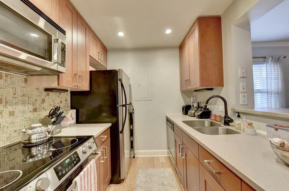 A tight renovated kitchen with a multicolored backsplash.