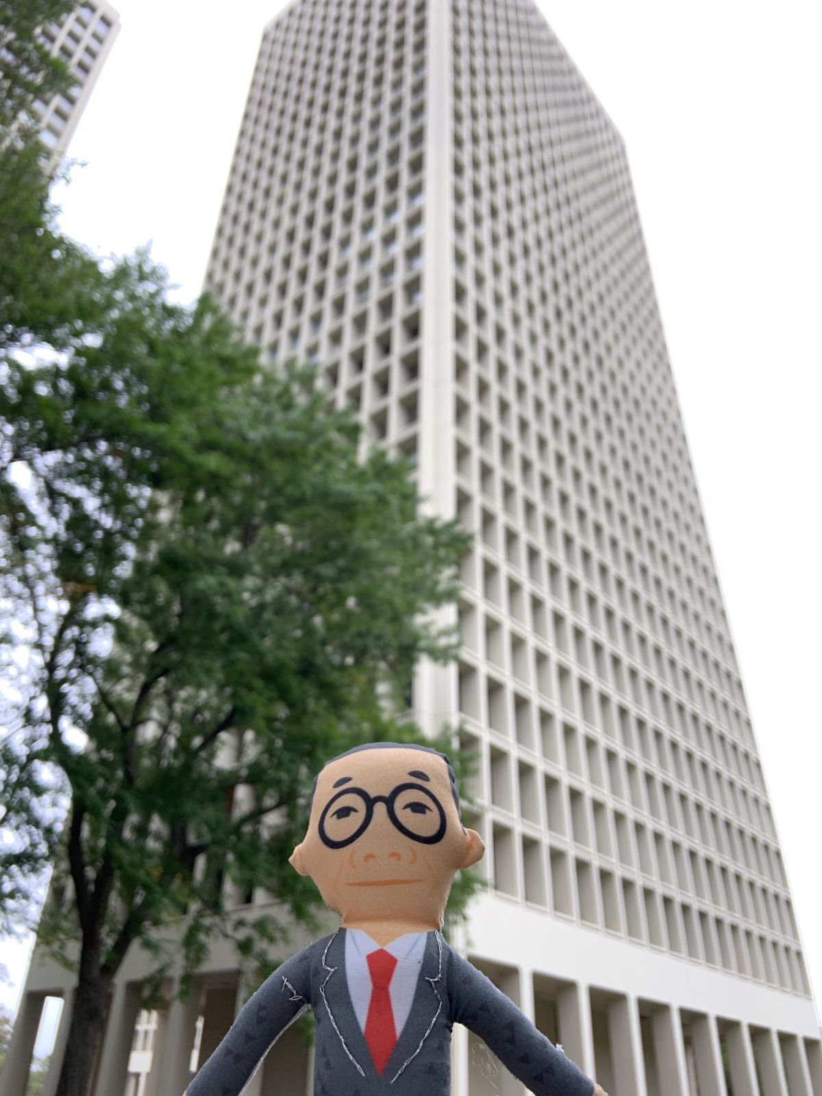 The small doll in front of a skyscraper with waffled facade.