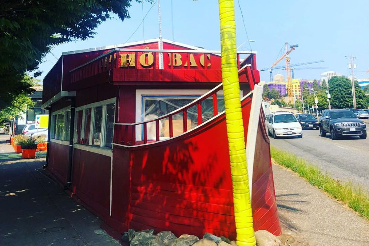 """The bright red exterior of the Pho Bac """"boat"""" restaurant with a yellow palm tree in front on a sunny day."""