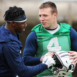 BYU quarterback Taysom Hill, right, talks with running back Jamaal Williams during practice in Provo Tuesday, March 1, 2016.