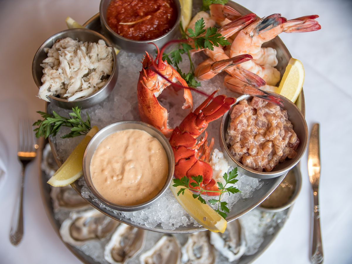 overhead view of a two-tier seafood tower with lobster tails, jumbo shrimp, crab salad, oysters, and more