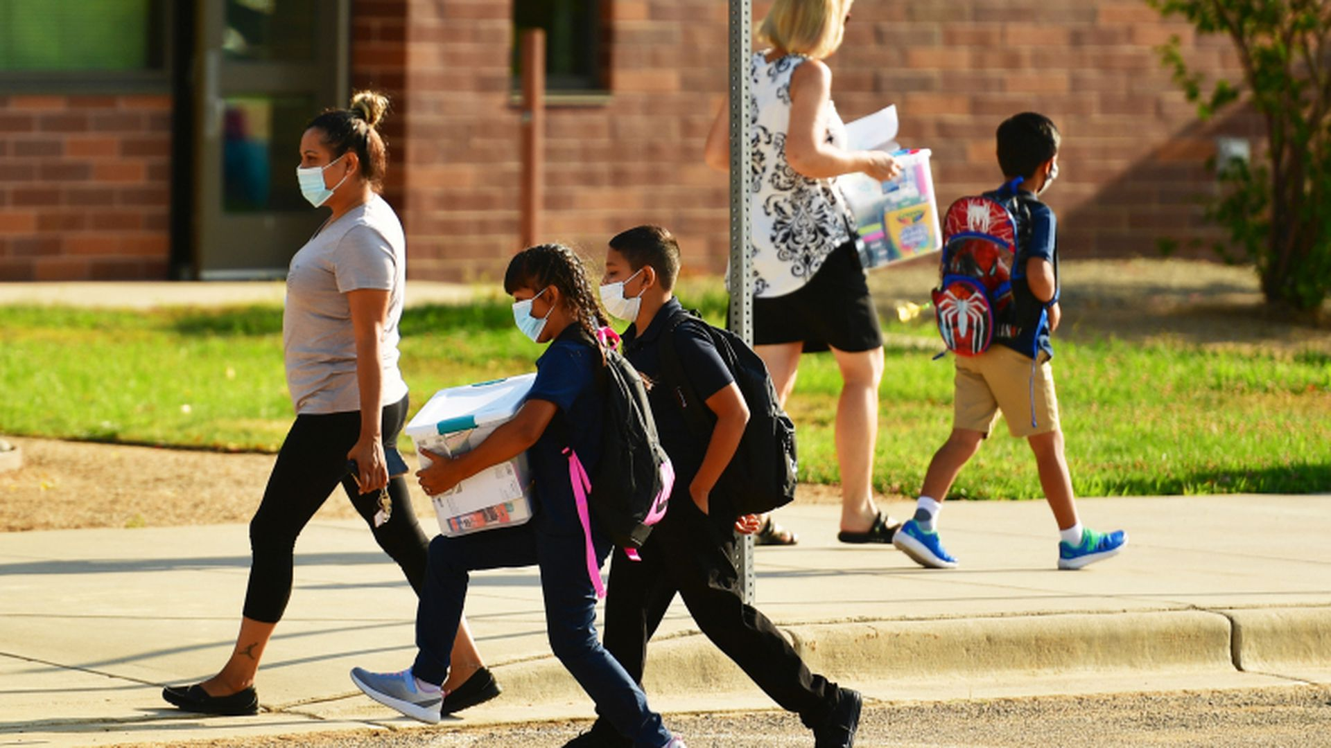 Parents and students wearing masks walk to school