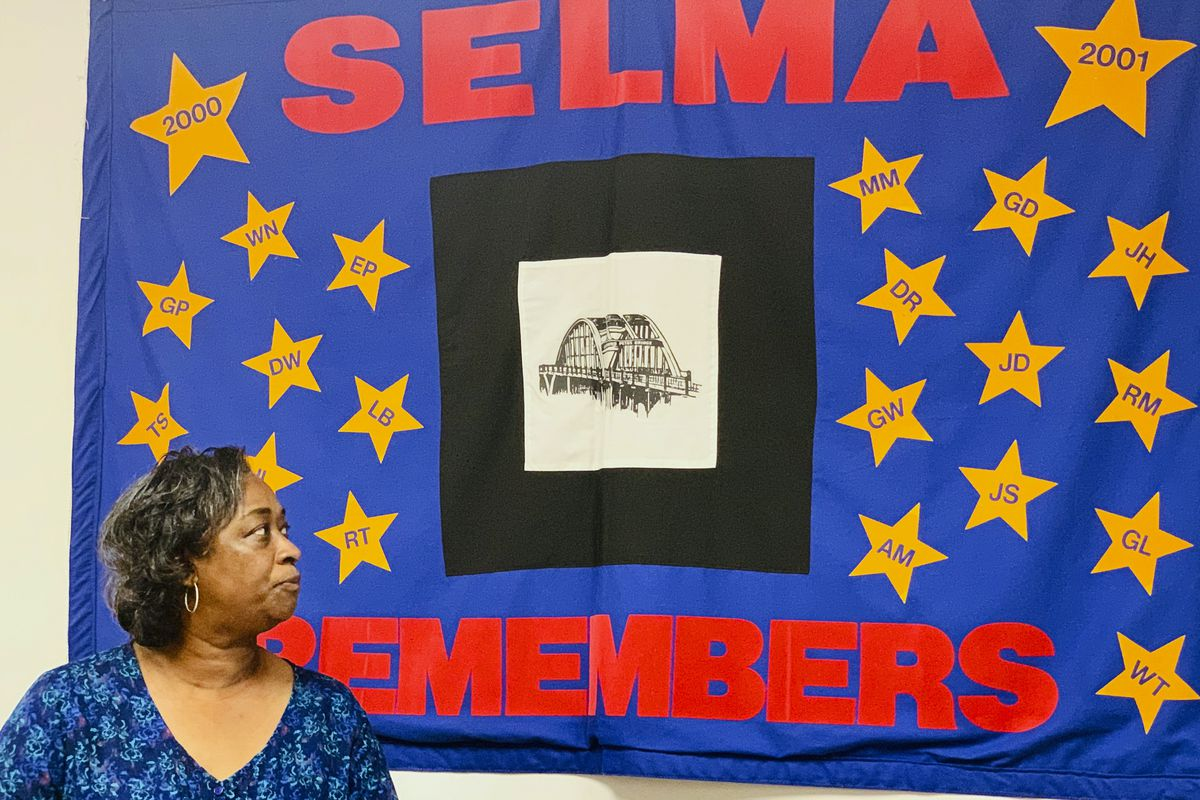 Mel Prince, executive director of Selma AIR, with a quilt that honors people who lost their lives to AIDS.