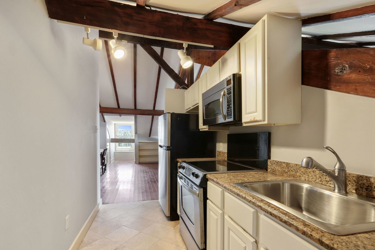 A kitchen with white cabinets, stainless steel stove and microwave, and granite counters.